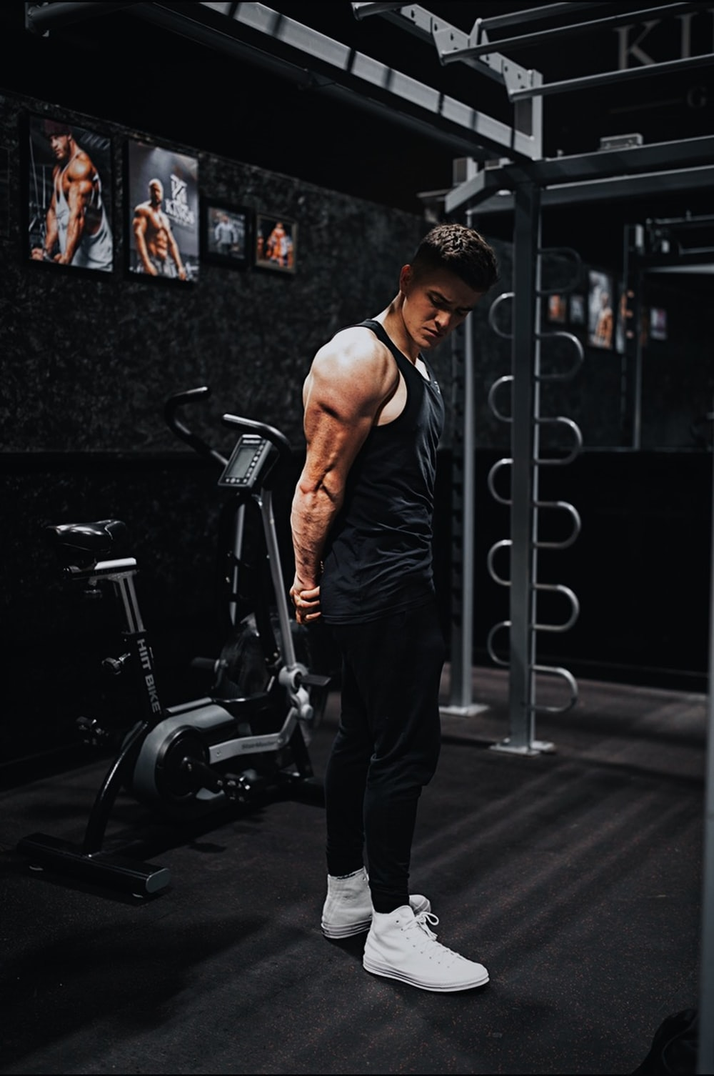 man in black tank top and black pants standing on black exercise equipment