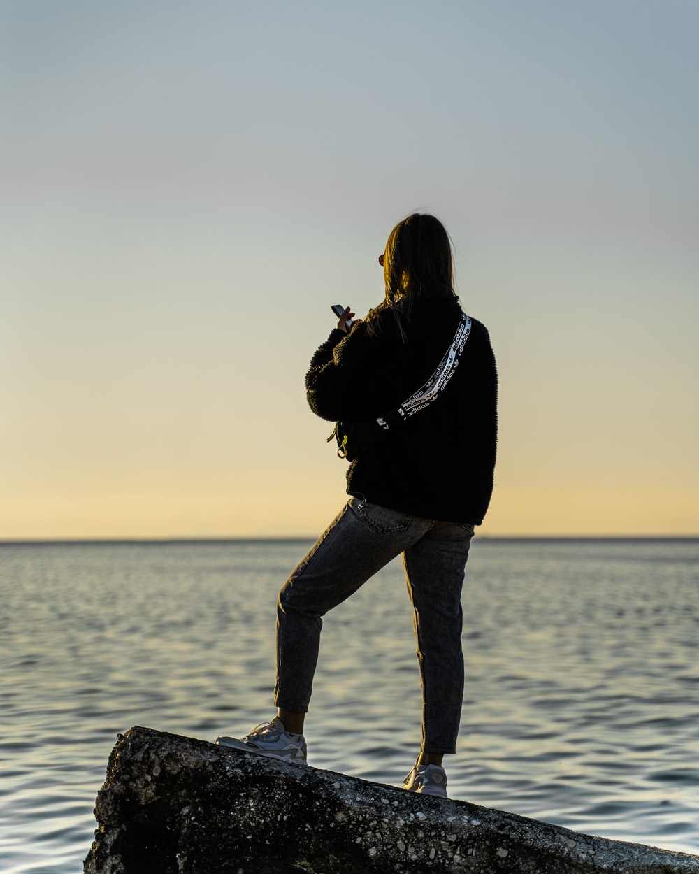 woman in black jacket and blue denim jeans standing on rock near body of water during