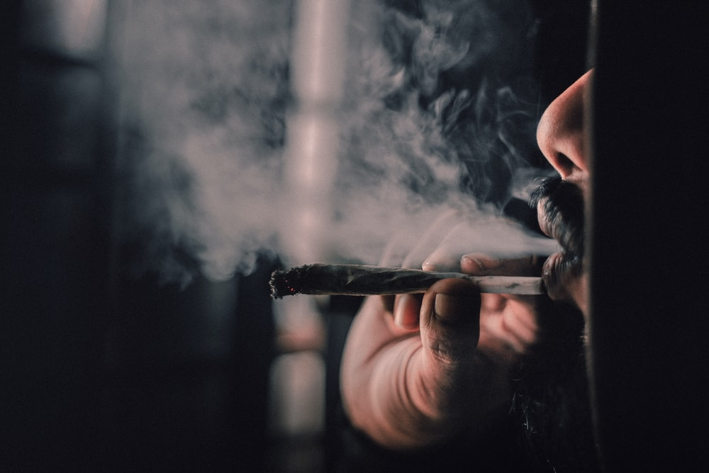 man smoking cigarette in close up photography