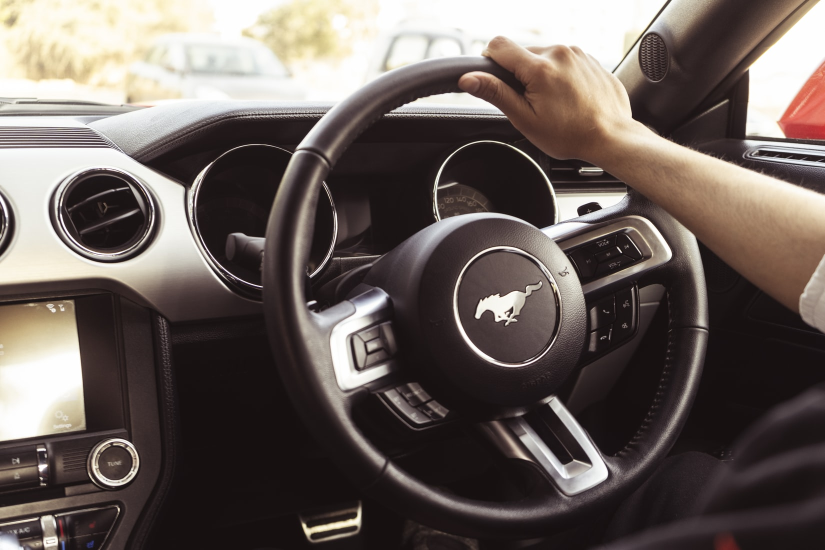 Person at the wheel of a Mustang