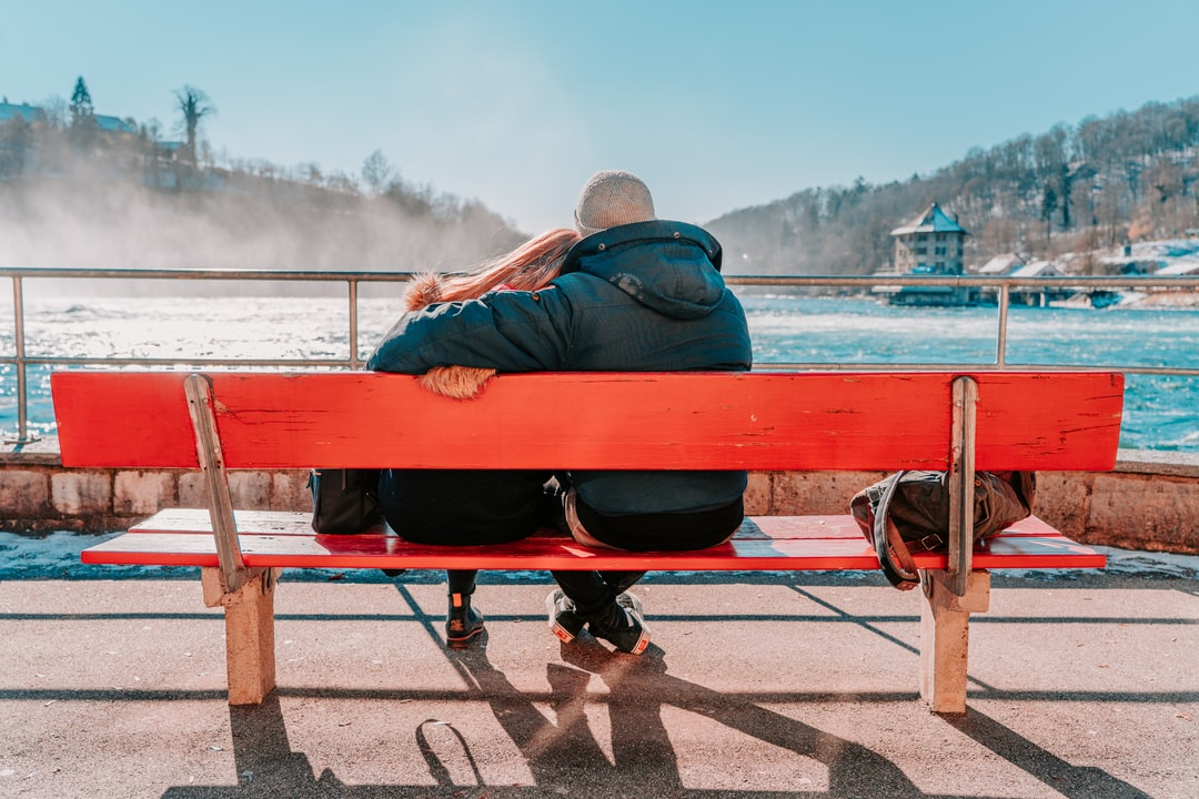 man in blue jacket sitting on red bench near body of water during daytime