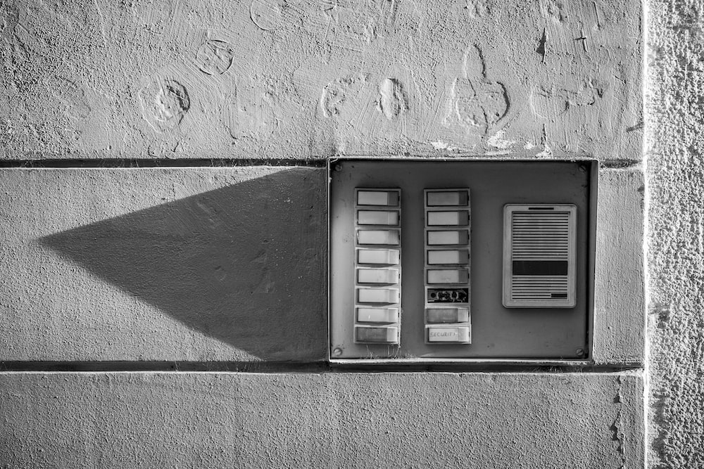 gray scale photo of a wall mounted telephone booth