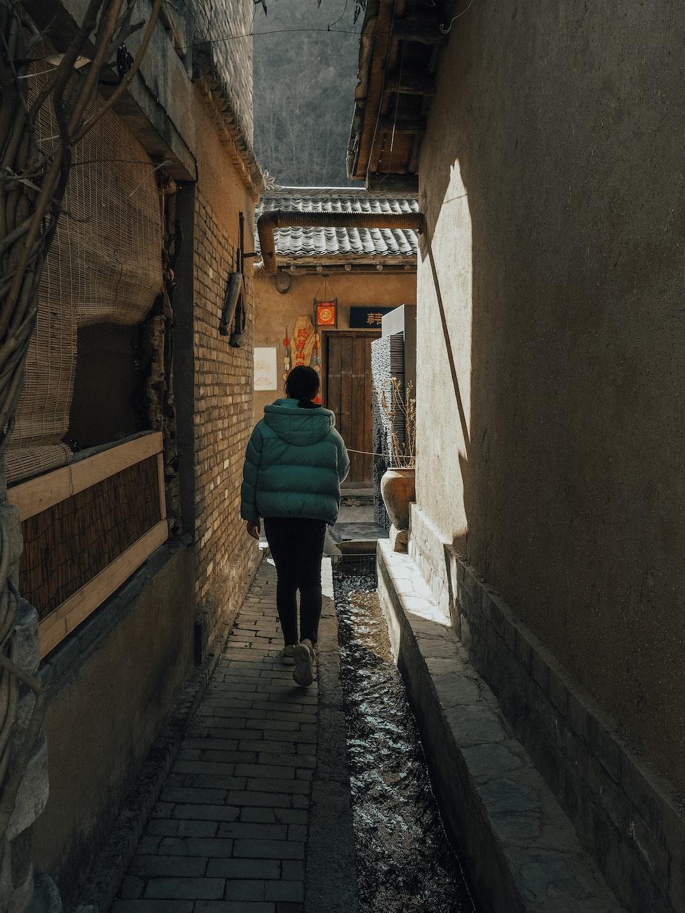 woman in green jacket walking on hallway