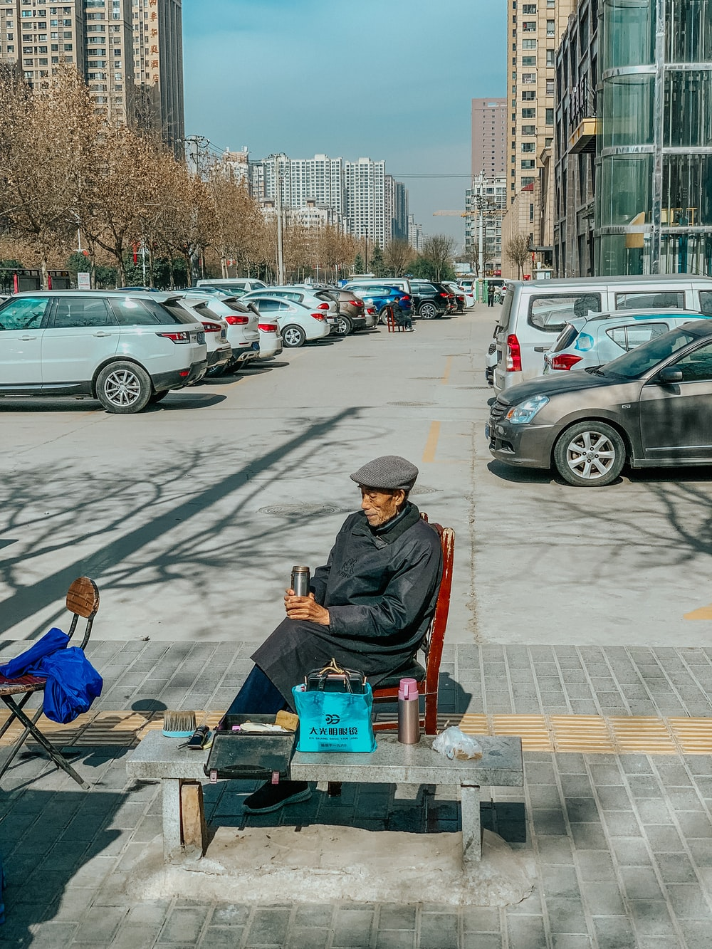 man in brown jacket sitting on chair reading book on street during daytime