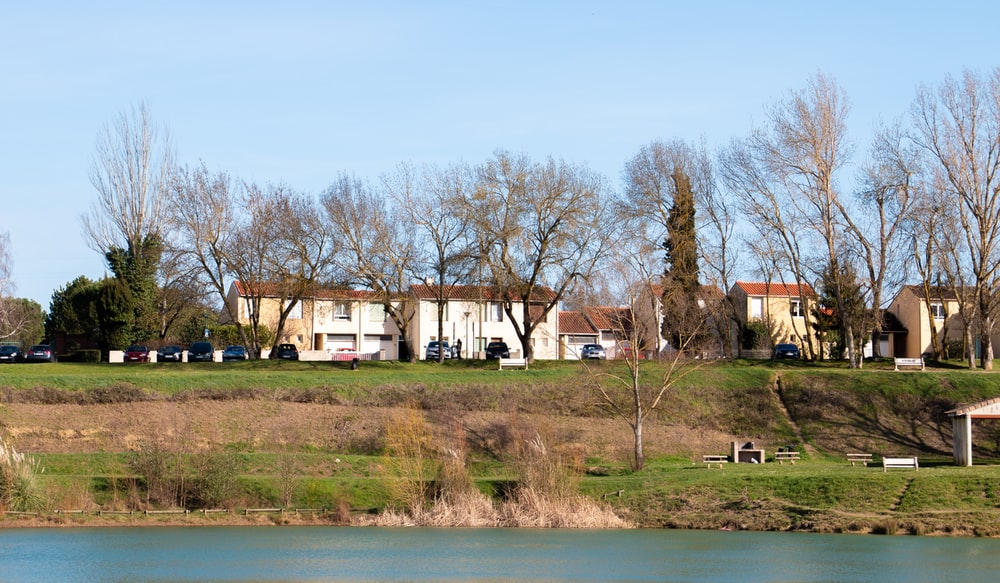 white and brown house near green trees and body of water during daytime