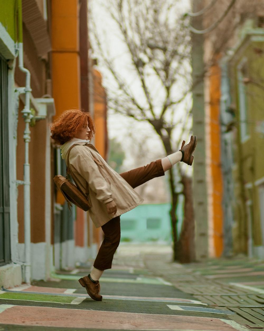 woman in brown jacket and black pants walking on sidewalk during daytime