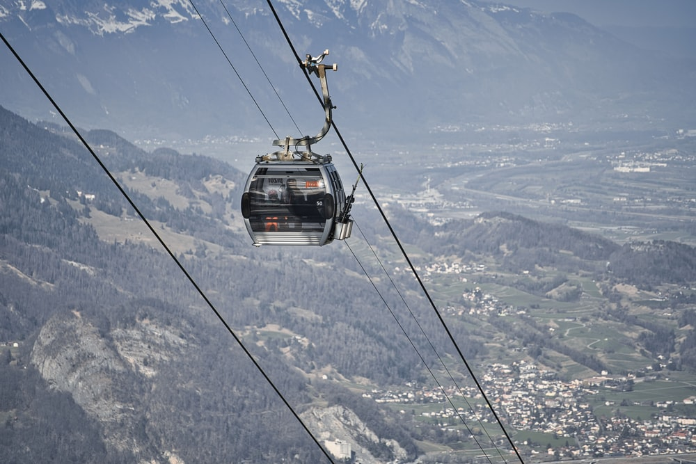 black cable car over snow covered mountain during daytime