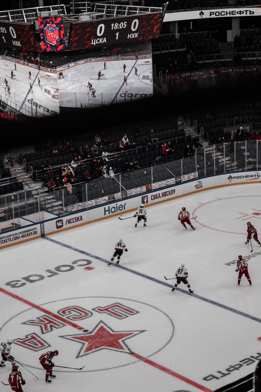 people playing ice hockey inside stadium