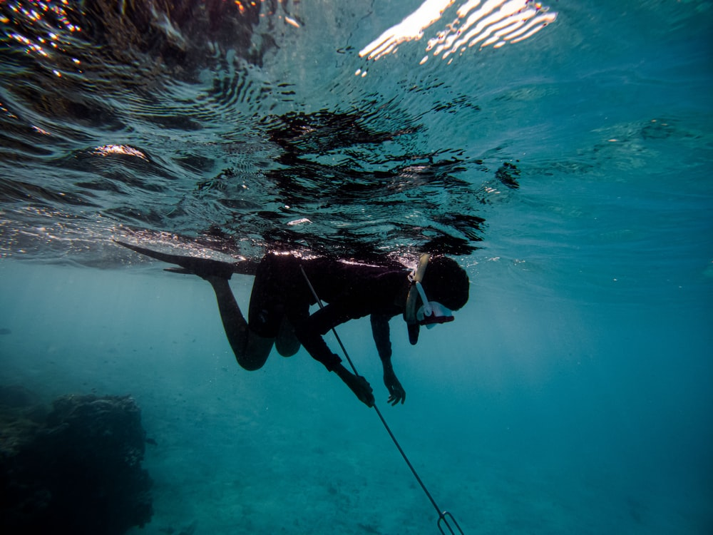 man in black wet suit swimming in water
