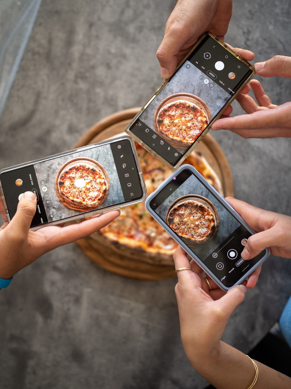 person holding black smartphone taking photo of pizza