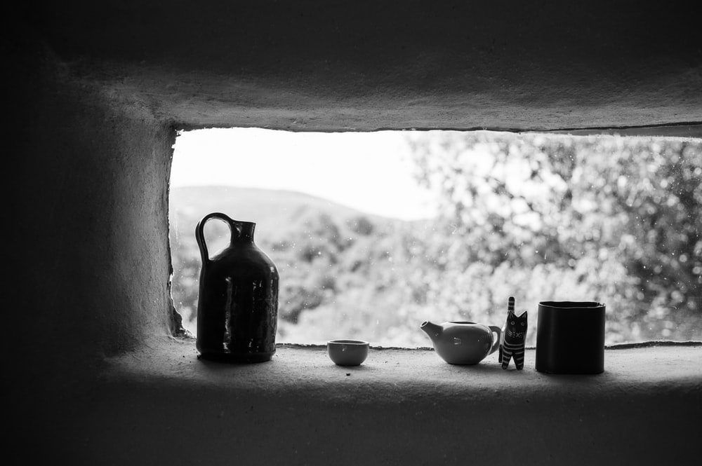 grayscale photo of ceramic teapot and teacup on table