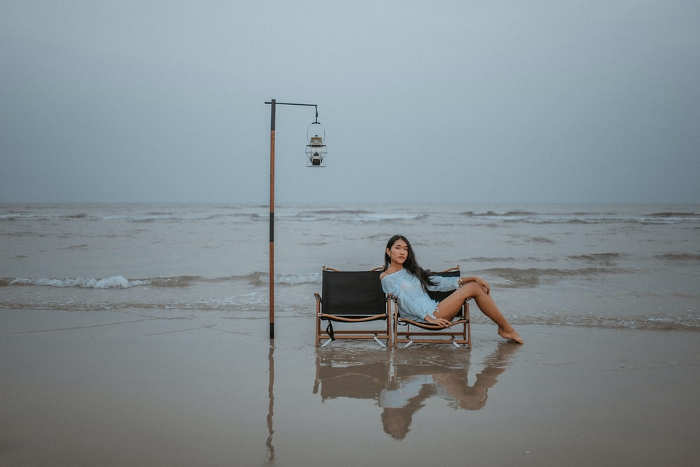 woman in white tank top sitting on black and gray chair on beach during daytime