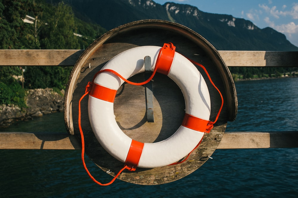 white and red inflatable ring on brown wooden dock during daytime