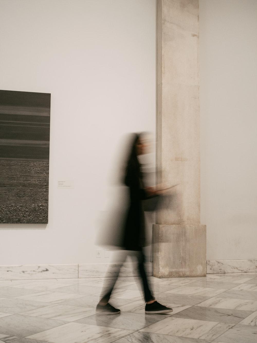 woman in black coat standing near white wall