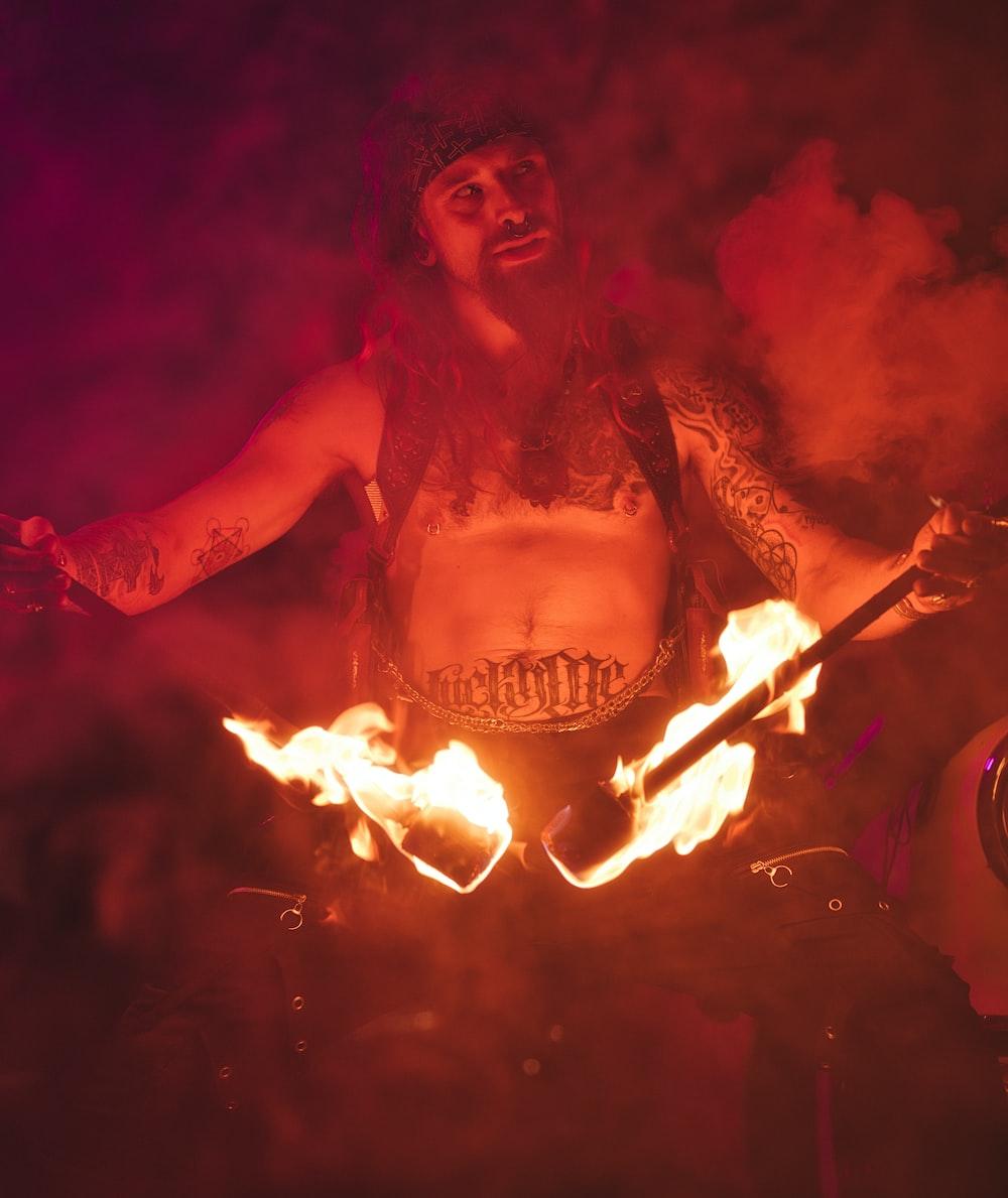 man in black tank top holding fire