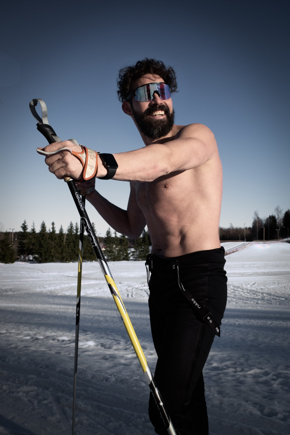 man in black shorts holding black and yellow ski pole