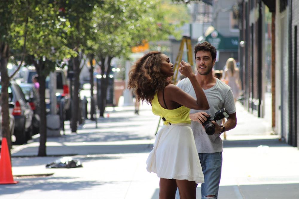 woman in white shirt carrying girl in yellow dress