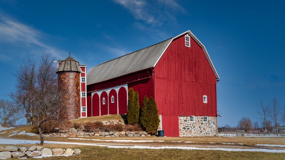 red wooden barn under blue sky during daytime