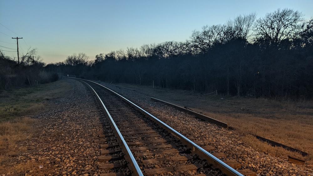 train rail near trees during daytime