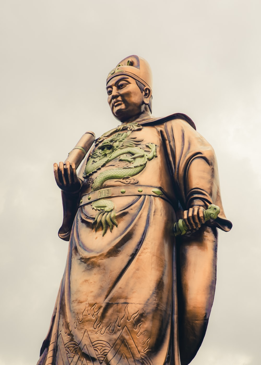 gold statue of man holding black and green stick