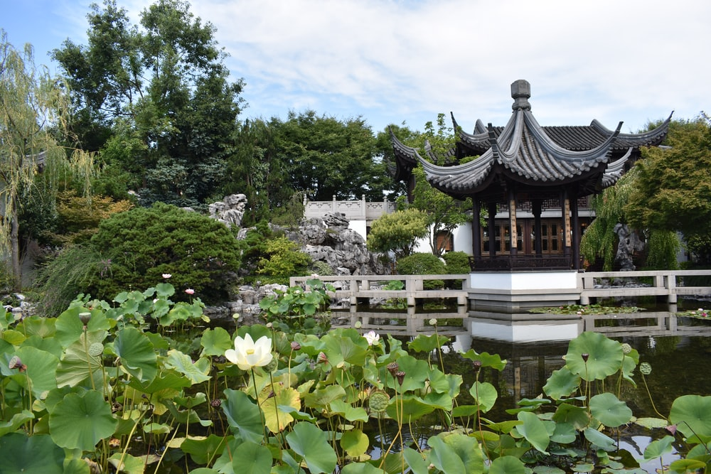 black and white temple surrounded by green trees under white clouds during daytime