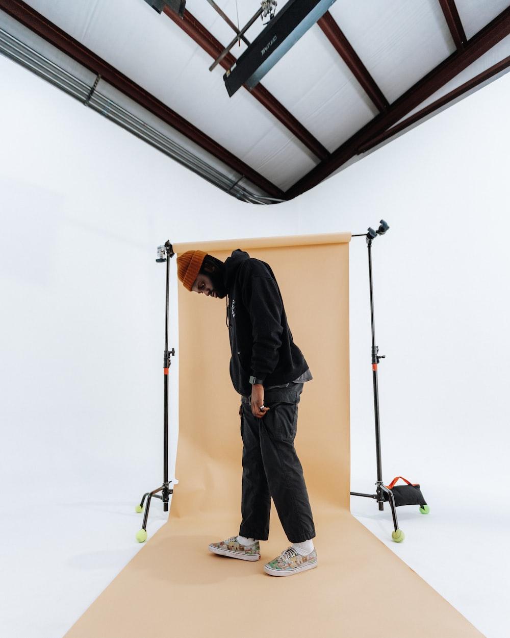 man in black jacket and blue denim jeans standing on brown wooden ladder