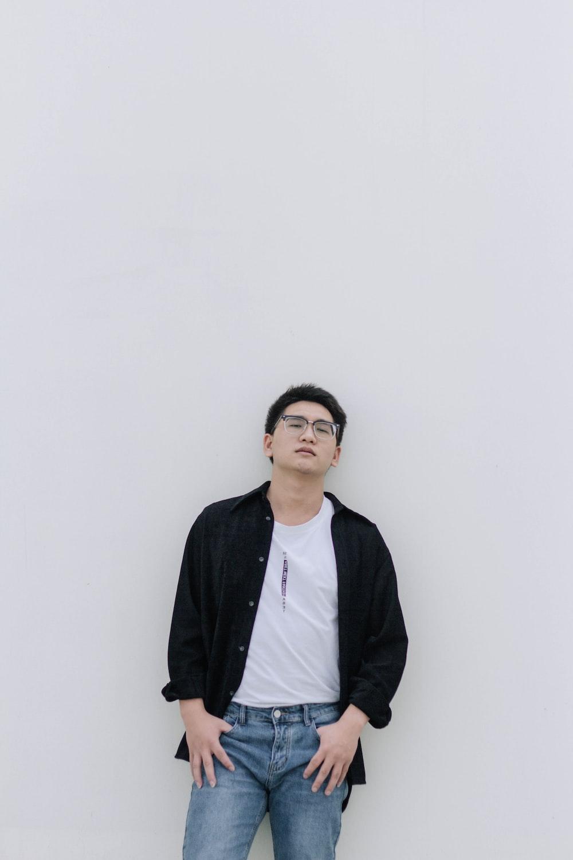 man in black jacket standing near white wall