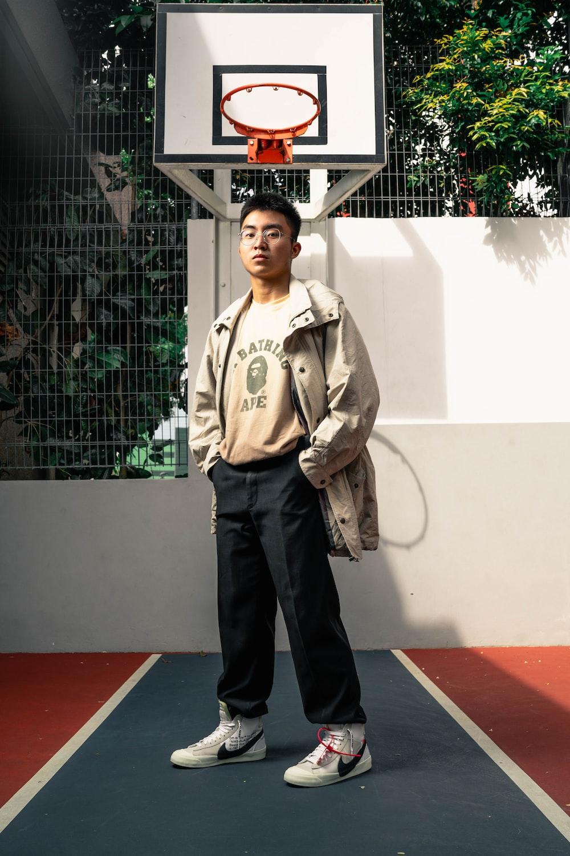 man in gray zip up jacket standing on red and black floor