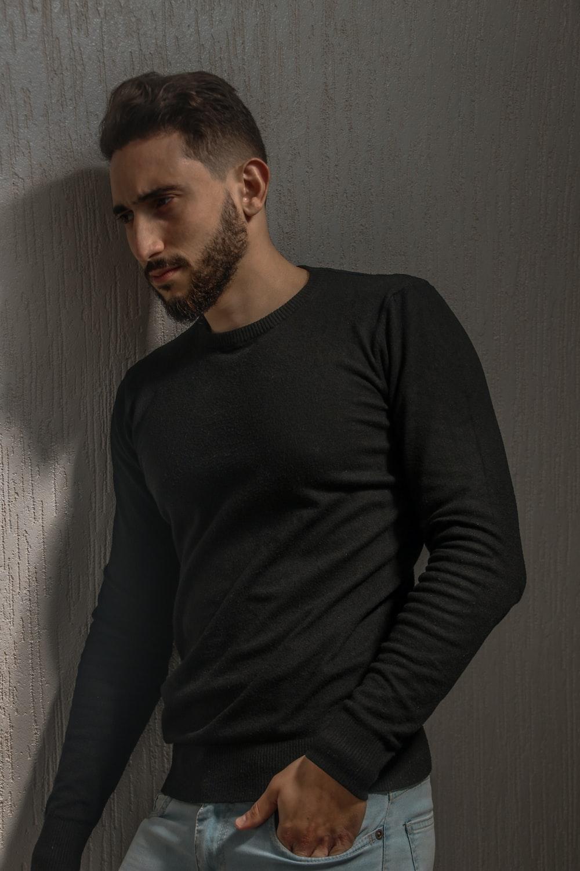 man in black long sleeve shirt standing beside white wall