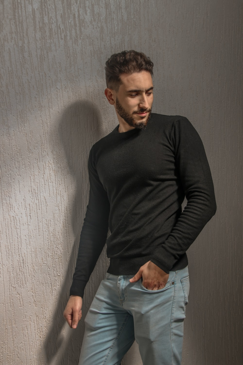 man in black long sleeve shirt and blue denim jeans