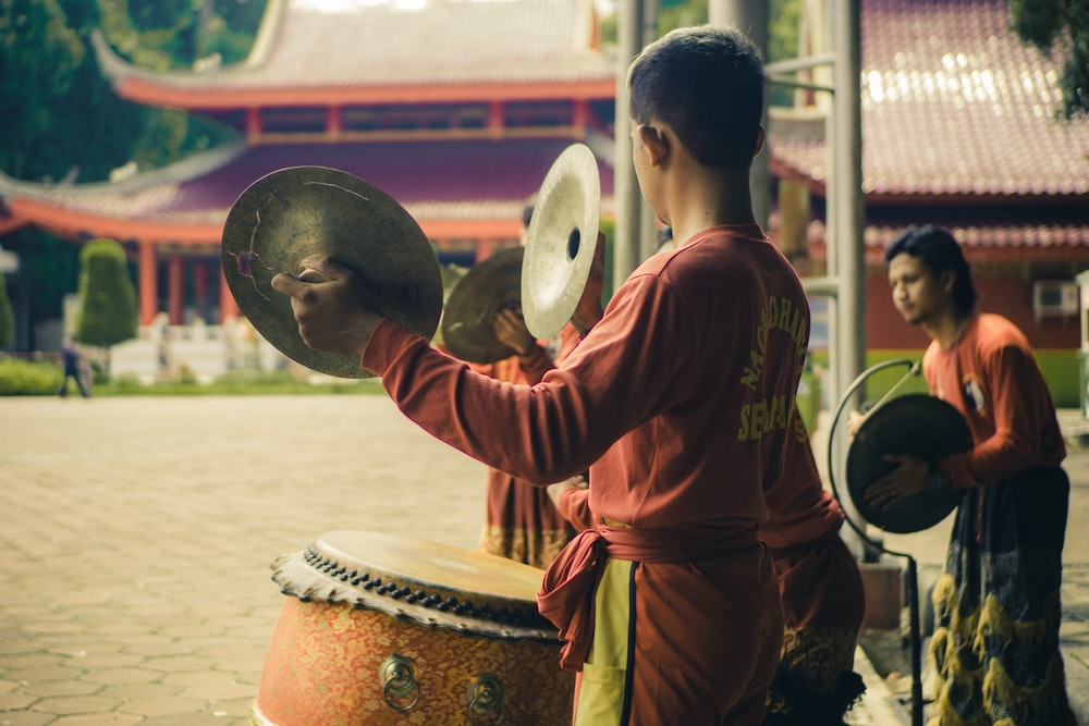 man in red long sleeve shirt playing drum
