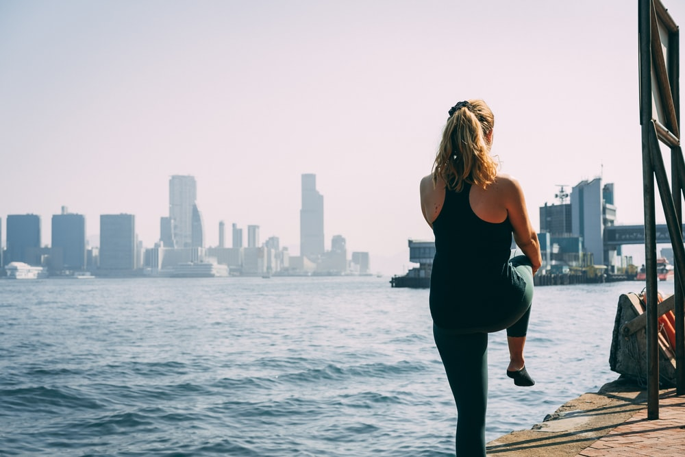 woman in black tank top and black pants standing on dock during daytime