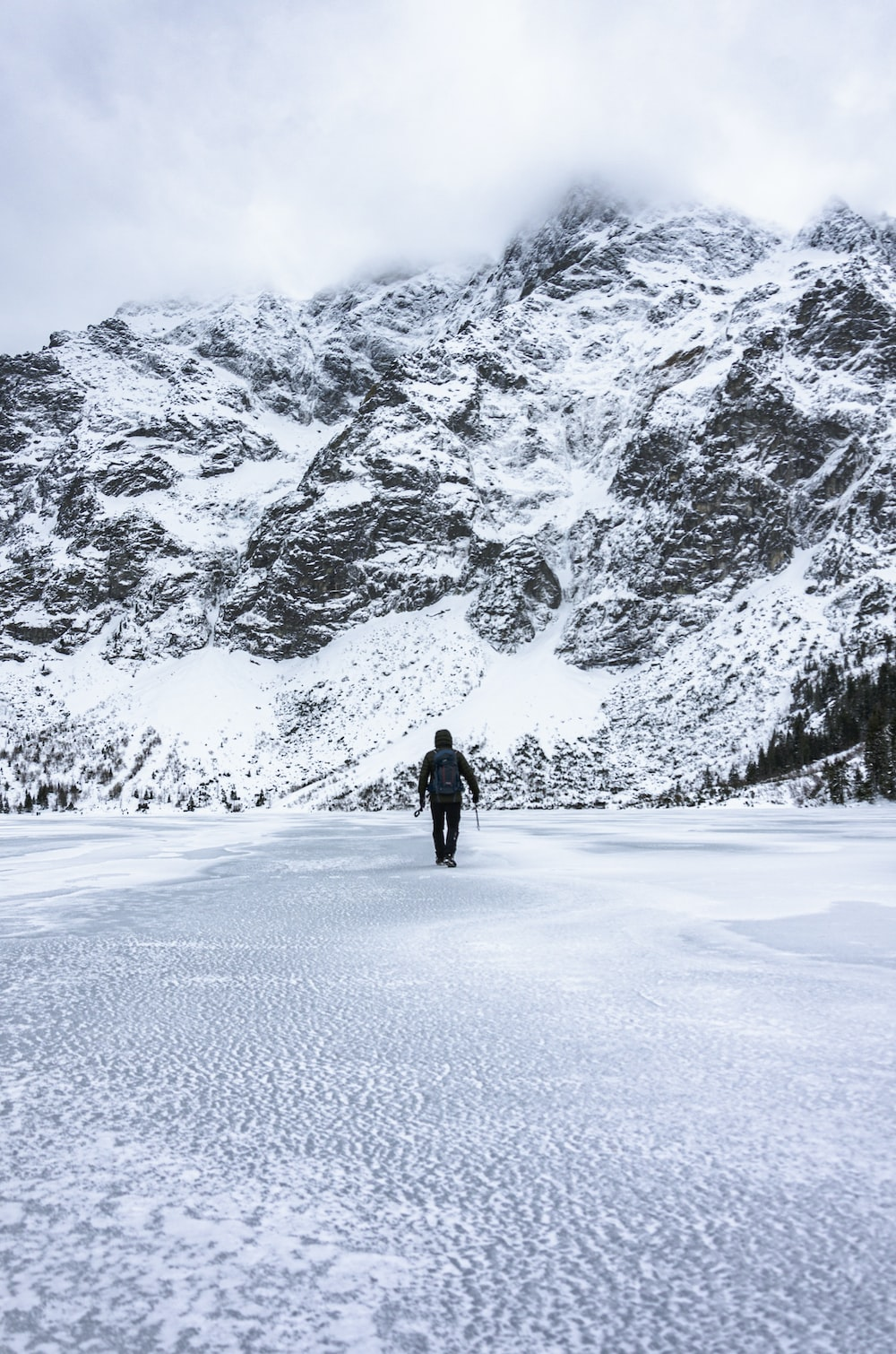 person in black jacket walking on snow covered ground during daytime