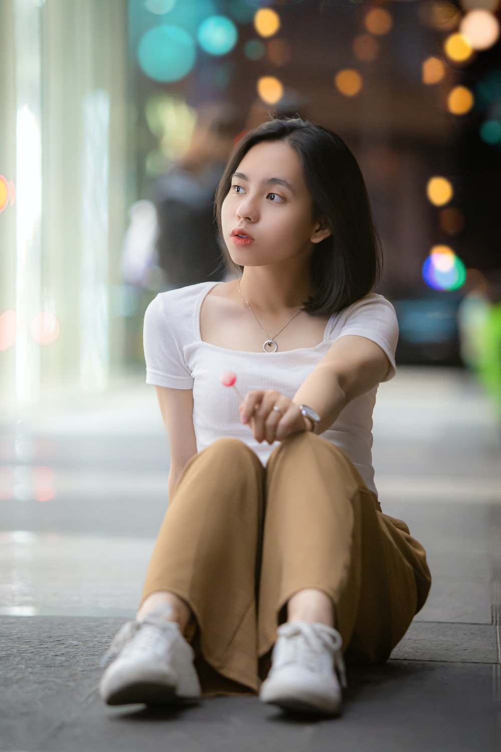 woman in white crew neck t-shirt and brown skirt sitting on floor