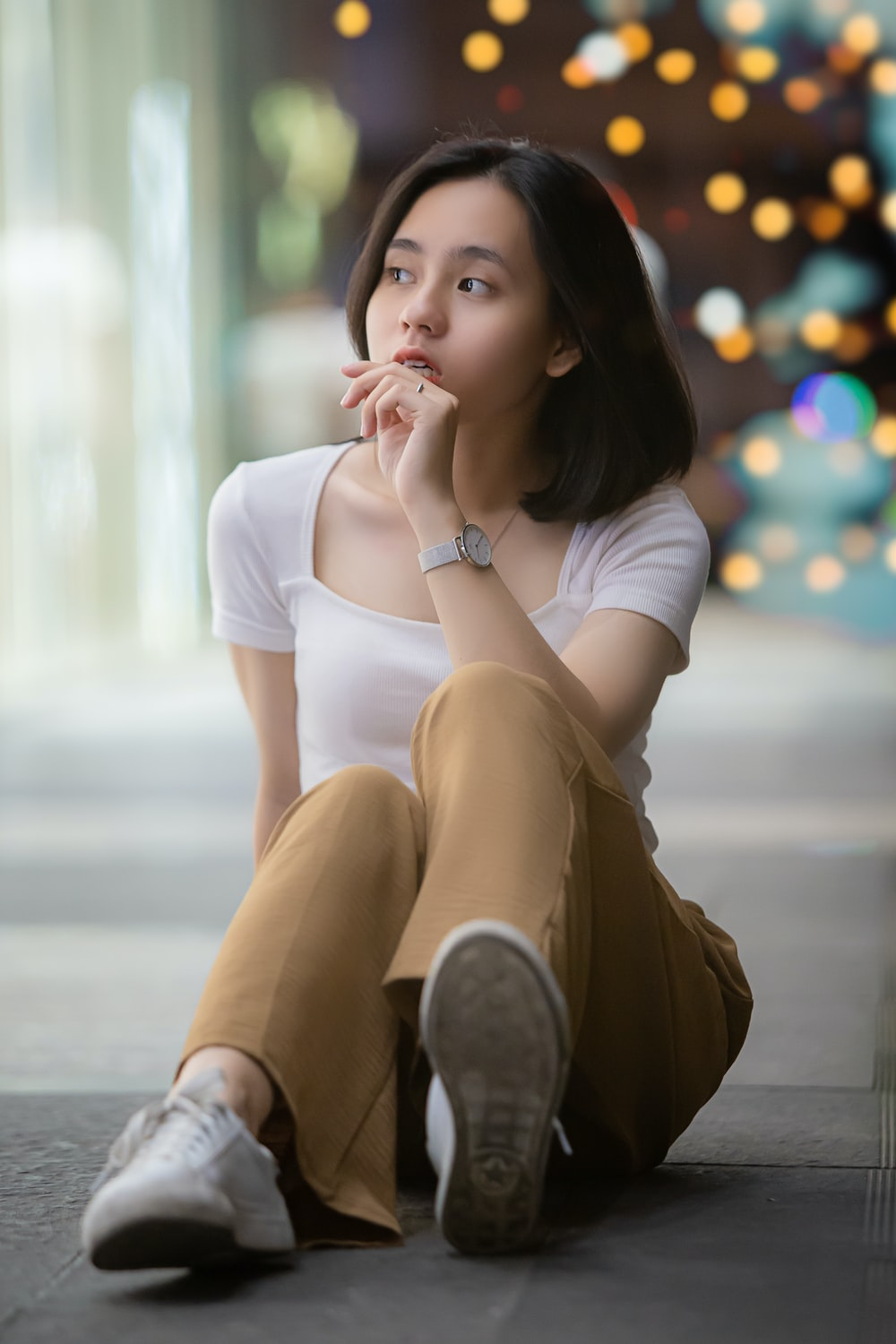 woman in white shirt and brown skirt sitting on floor