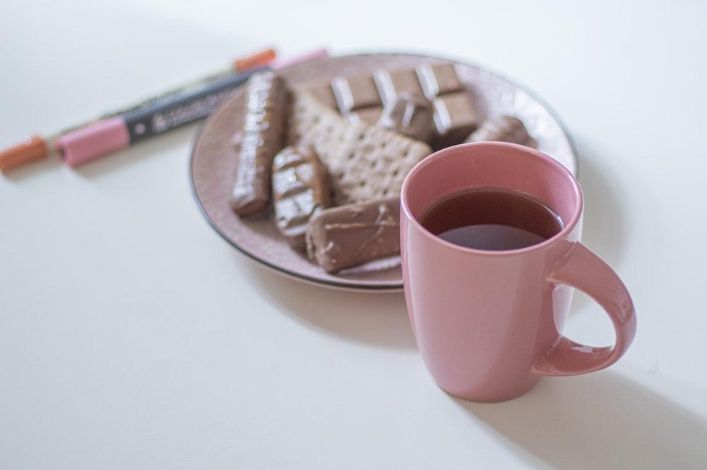 pink ceramic mug on brown wooden tray