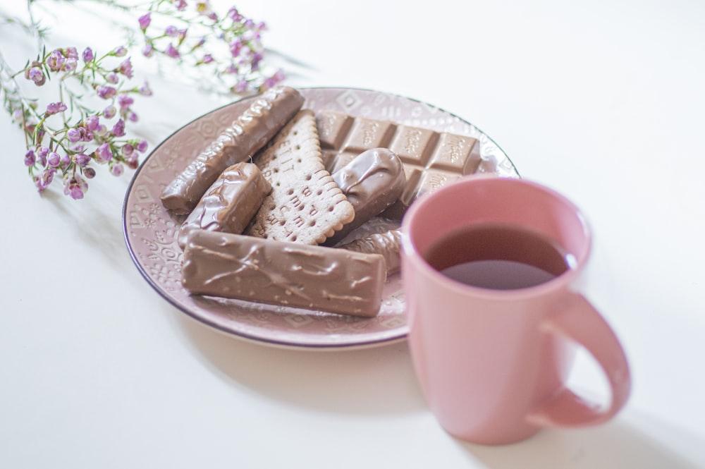white ceramic mug on pink ceramic saucer