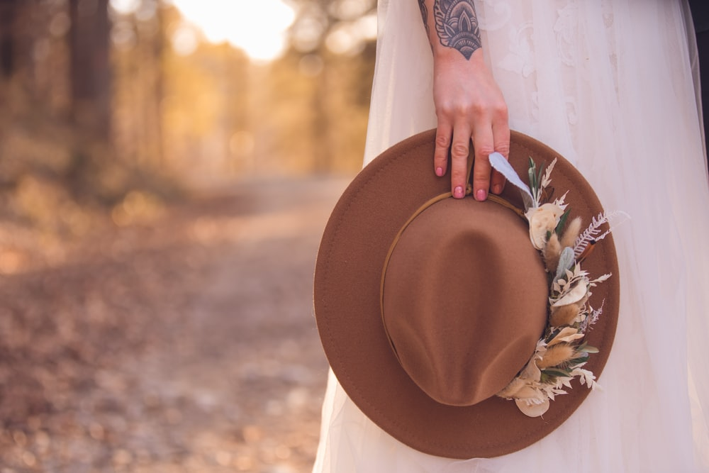 woman in white long sleeve shirt holding brown hat