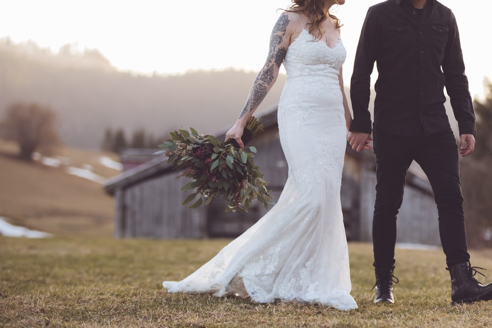 woman in white wedding gown standing beside man in black suit