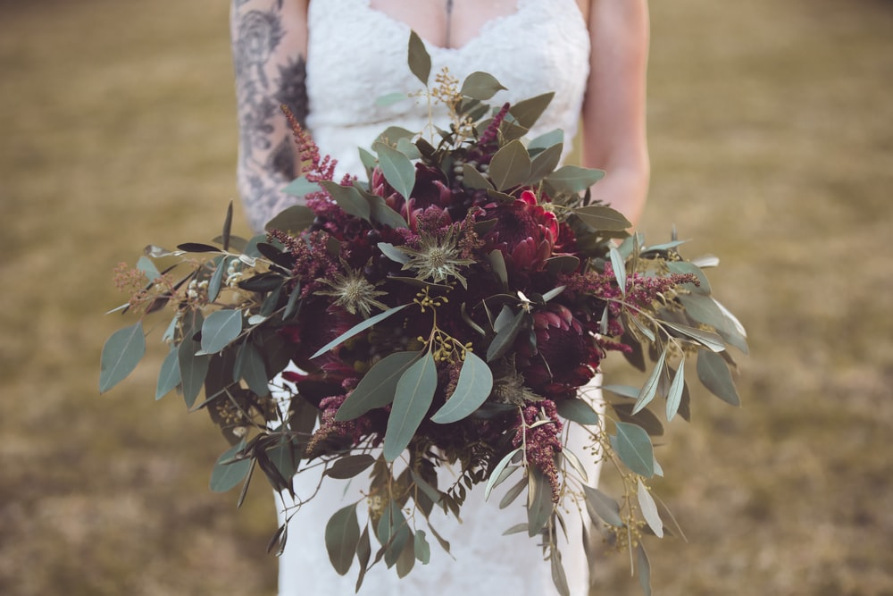 woman in white floral lace wedding dress holding red and green plant