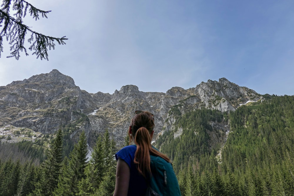 woman in blue shirt standing near green trees and mountain during daytime