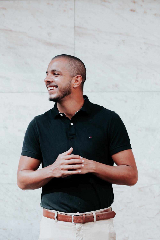 man in black polo shirt standing near white wall