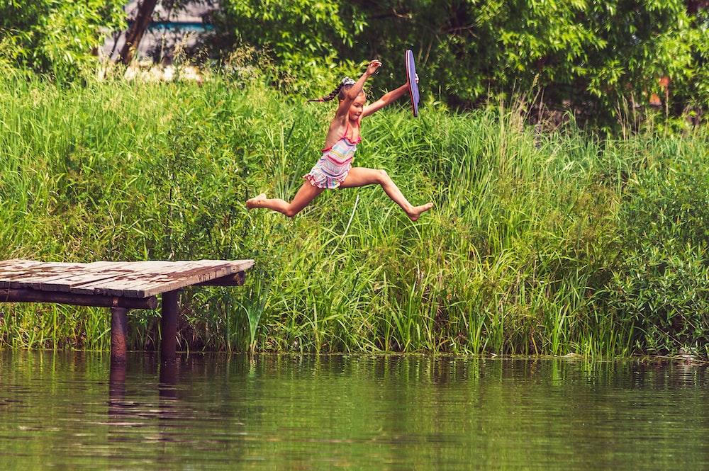 woman in bikini lying on wooden dock during daytime