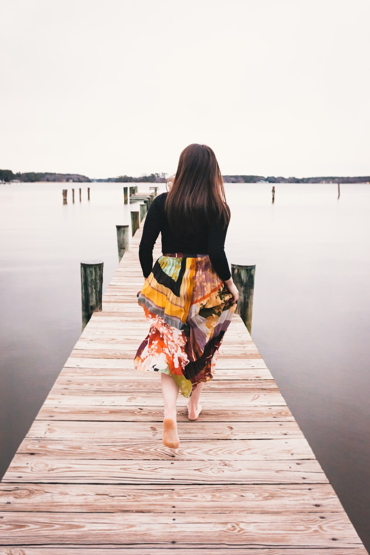 woman in black long sleeve shirt and orange skirt walking on wooden dock during daytime