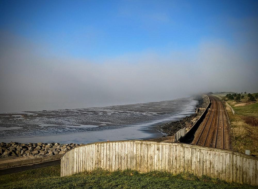 brown wooden fence on green grass field near sea