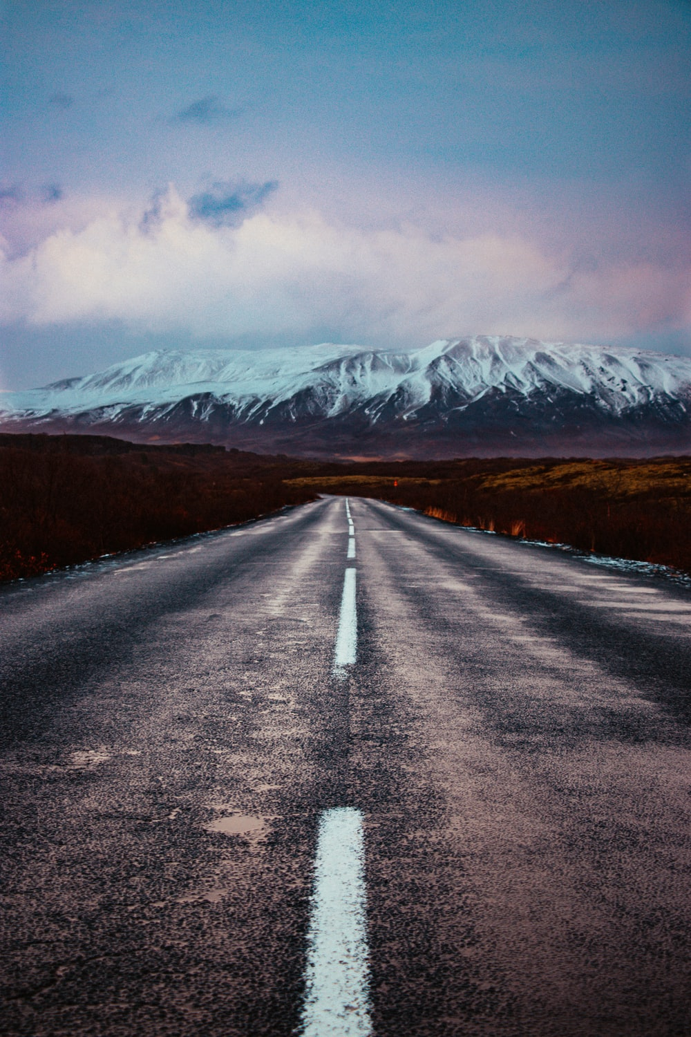 gray asphalt road between brown grass field near snow covered mountain during daytime