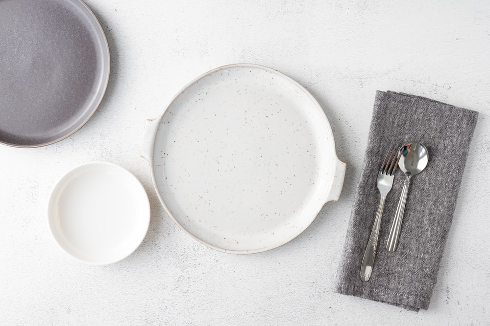 white round plate beside fork and bread knife
