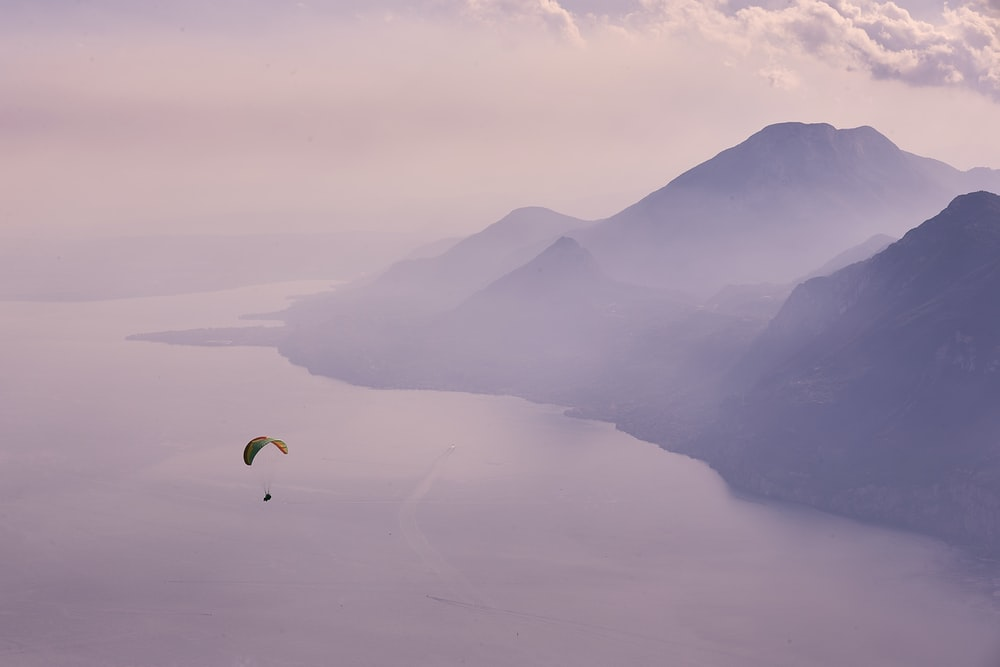 person in parachute over mountains during daytime