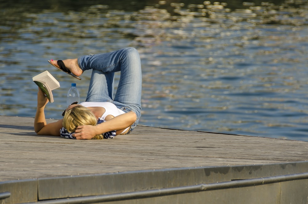 woman in white tank top and gray pants lying on brown wooden dock during daytime