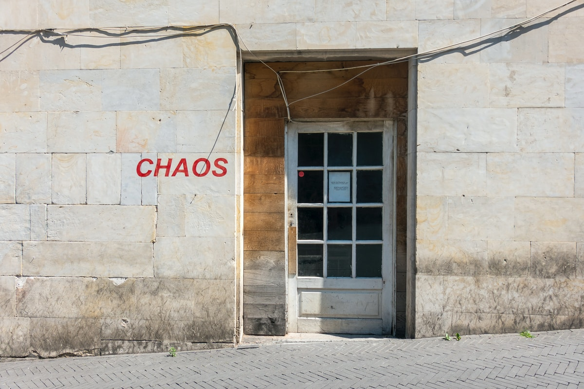 A light concrete building with the word CHAOS in red. Inset is a white door framed with faded wood.  The door has twelve glass panes and there is a piece of paper in the middle of the 2nd row. There is a grey herringbone walkway sloping down the building.